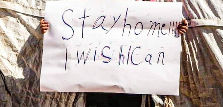 """Stay home, I wish I could"" – Kind in Syrien mit einem Schild"
